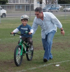 dad_helping_boy_ride_bike